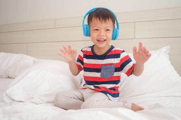 Улыбающийся азиатский малыш мальчик в полосатой футболке слушает музыку в наушниках и танцует