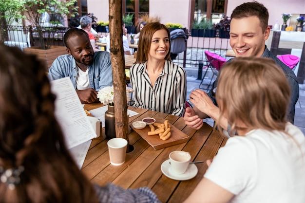 Веселые разговоры с близкими друзьями на ужине в жаркий весенний день в кафе