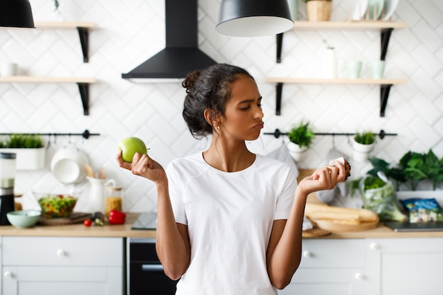 Африканская женщина держит яблоко и булочку и думает, что выбрать