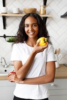 Улыбчивая женщина-мулатка, одетая в белую футболку, с красивым лицом и распущенными волосами, держит в руке желтый перец возле кухонного стола на современной кухне