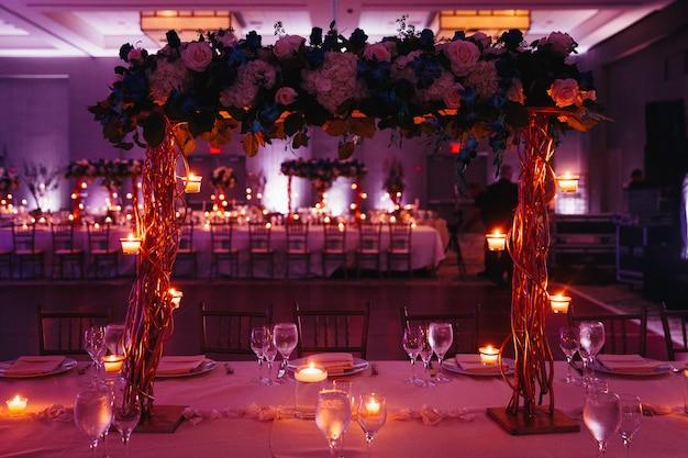 Красивая розовая декорированная свадебная сервировка с центральным украшением и свечами