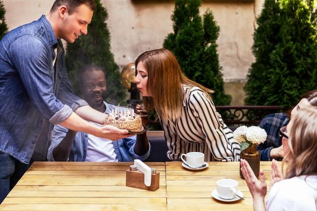 Именинница задул свечи на торте, который держит красивый молодой мальчик
