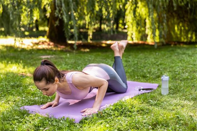 Фитнес девушка качает пресс на открытом воздухе в парке