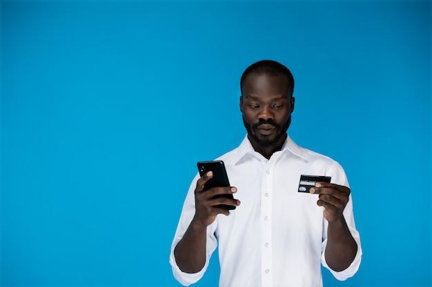 思慮深いひげを生やしたアフロアメリカンの男は携帯電話を保持し、クレジットカードを探しています