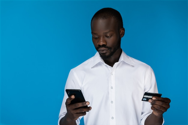 前景の思慮深いひげを生やしたアフロアメリカンの男は携帯電話を見ているとクレジットカードを保持
