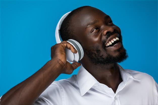 笑みを浮かべて男は音楽を聴くことを楽しんでいます