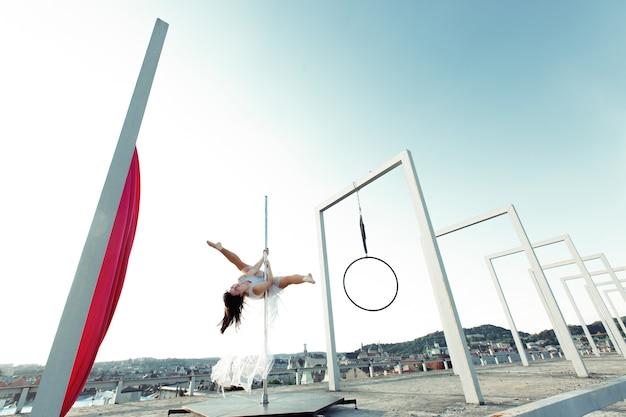 屋外の屋上でパフォーマンスする美しいセクシーなポールダンサー