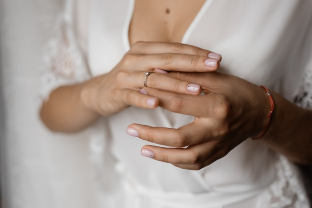 Руки невесты с обручальным кольцом с бриллиантом и нежным маникюром