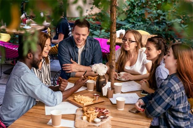 屋外の居心地の良いレストランで親友の友好的な会議のテーブルに美味しい食べ物