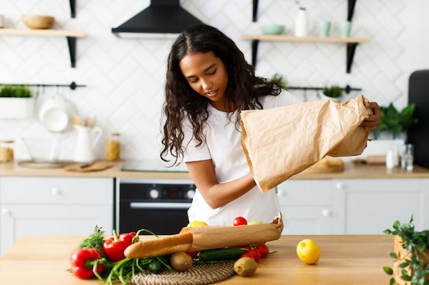 笑顔の美しいムラートの女性は、モダンなキッチンのテーブルで新鮮な野菜から食事を作る準備をしています