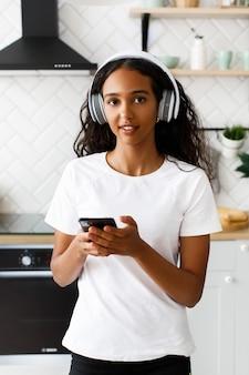若いアフロ女性がキッチンに立って、ヘッドフォンで音楽を聴く彼女の手に携帯電話を保持