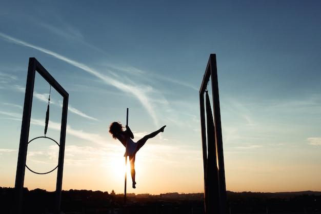 日没時に屋根の上で実行セクシーなポールダンサーのシルエット