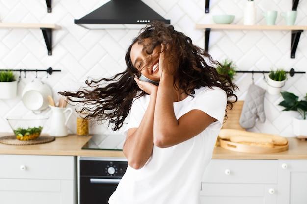 大きなワイヤレスヘッドフォンで巻き毛の笑顔の混血女性が台所で目を閉じて踊っています。