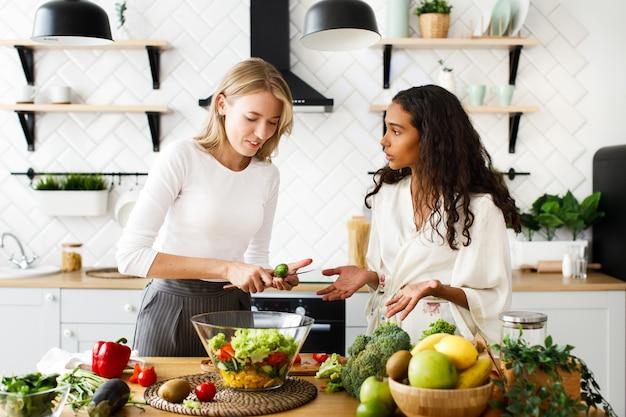 Две женщины разных национальностей разговаривают и готовят на кухне