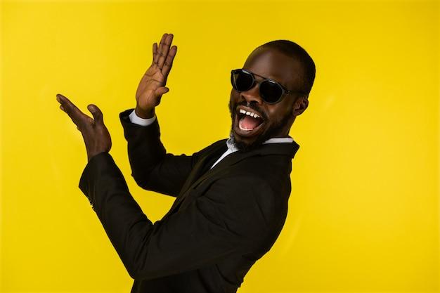 Роскошный бородатый молодой афроамериканец хлопает в ладоши в темных очках и черном костюме