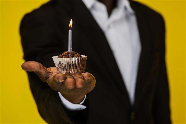 Кекс с горящей свечой на руке афроамериканца на желтом фоне