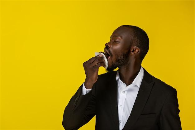アフリカ系アメリカ人の若い男はカップケーキを食べています