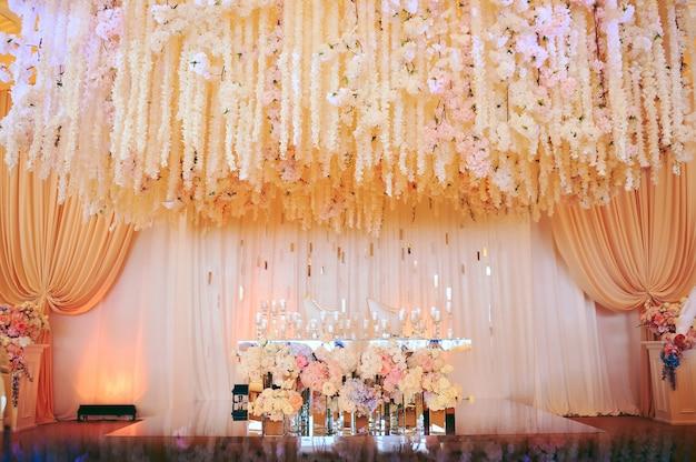 Свадебный стол жениха и невесты украшен цветами и свечами
