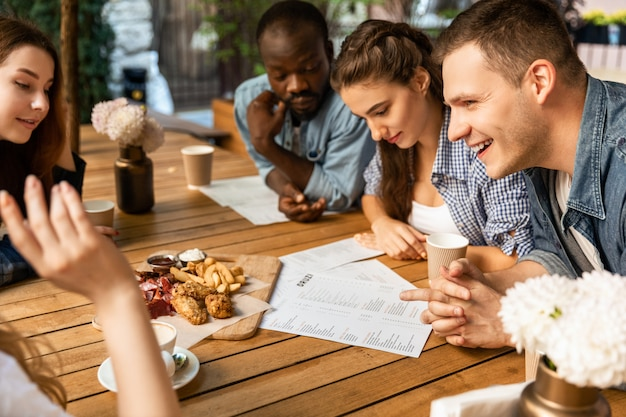 若者は小さな居心地の良いオープンエアのカフェで注文する前にメニューを学んでいます