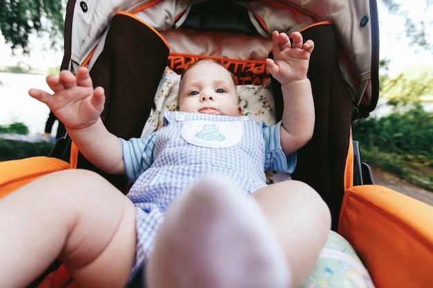ベビーカーのスタイリッシュな服でかわいい青い目の赤ちゃん少年