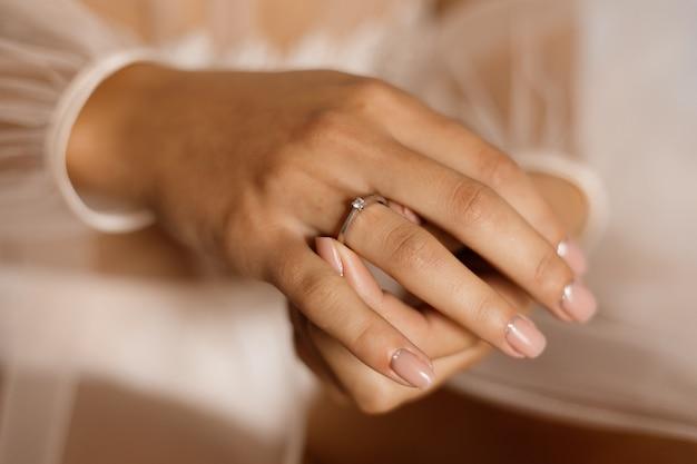 ダイヤモンドと美しいマニキュアの婚約指輪を持つ女性