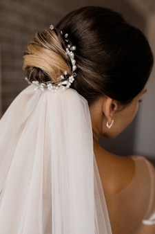 ベールを持つブルネットの女性の結婚式の髪型