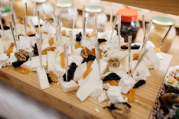 木製の机の上にチーズやドライフルーツのようなスナックがあります。
