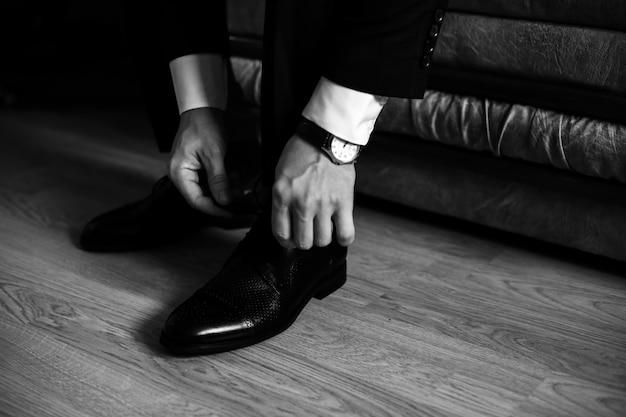 Мужчина завязывает шнурки на своей обуви