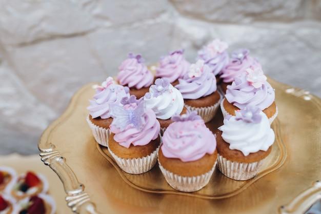 かすかなピンクのクリームで覆われたカップケーキと黄金のトレイ