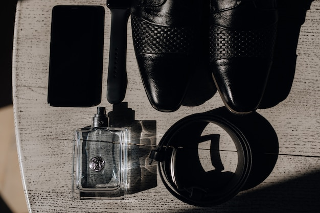 木製の表面の靴、ベルト、香水、電話