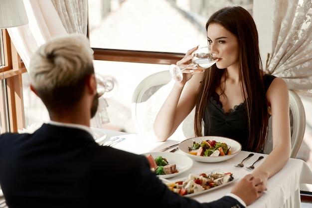 女と男はレストランでロマンチックなデートに手をつないでいます。
