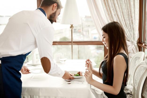 レストランでハンサムなウェイターは若い女性に食事を提供しています