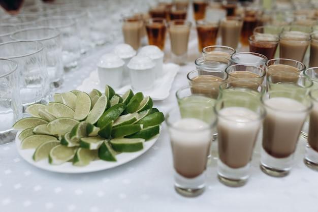 Маленькие бокалы с напитками и тарелка с ломтиками лайма