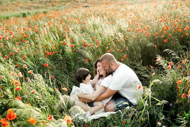 魅力的な家族がケシ畑の中で座って楽しんでいます