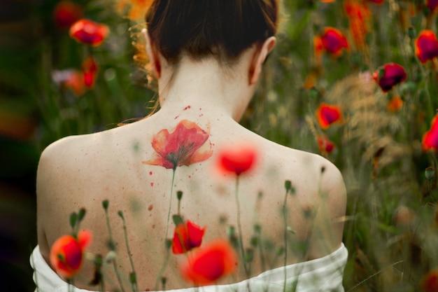 裸の背中とそれに花を持つ美しい女性