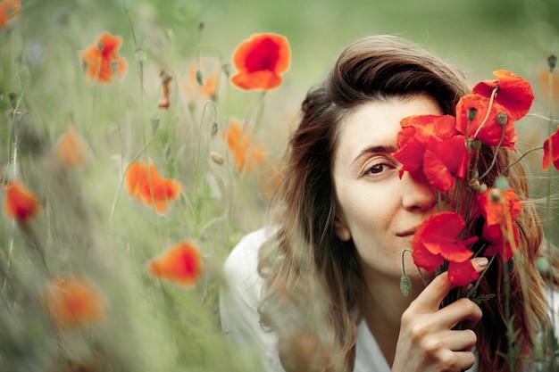 女性はケシの花の花束で顔を覆っています。