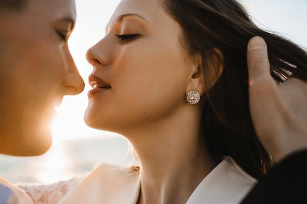 晴れた日の屋外で若い美しい白人カップルのキスの前の瞬間