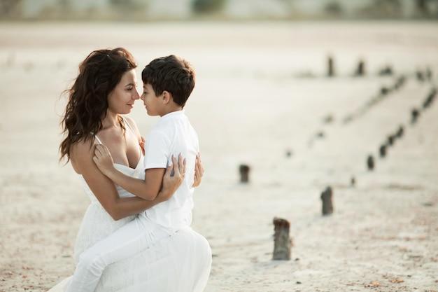 Прекрасный портрет матери и сына на песке, одетый в белую одежду, глядя друг другу в глаза