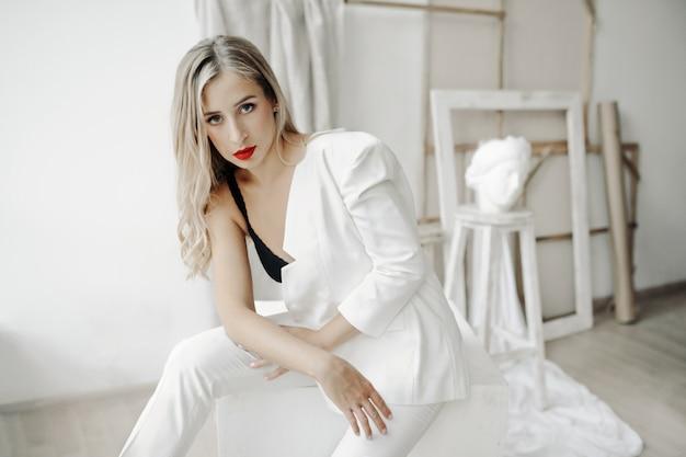 Красивая девушка в лифчике и белом костюме на одном плече сидит на белом кубе