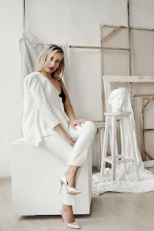 Красивая девушка в белом костюме сидит на белом кубе в галерее
