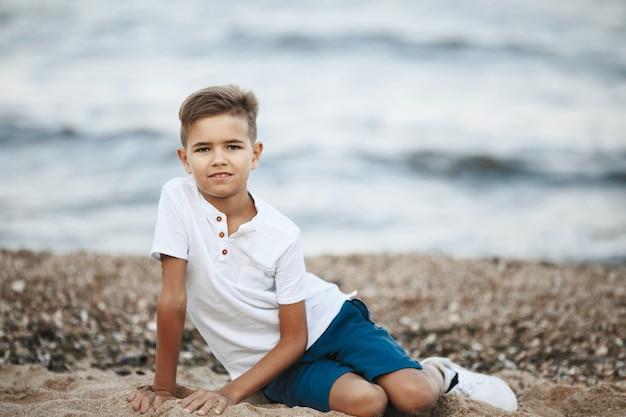 Маленький кавказский мальчик сидит на пляже у моря и смотрит прямо, одетый в повседневную одежду