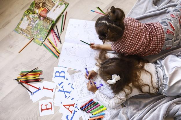 Вид сверху двух крошечных девушек, которые рисуют в книжке-раскраске, лежащей на полу на одеяле
