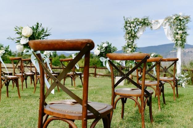 白いトルコギキョウと茶色のキアヴァリ椅子の屋外と結婚式の儀式アーチから花飾りの正面図