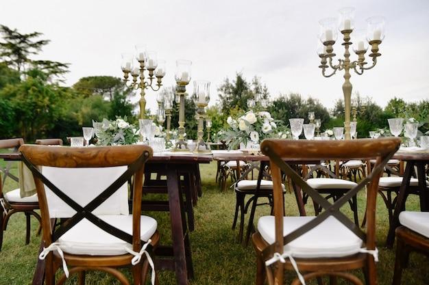 花の組成で飾られた結婚式のお祝いテーブルと茶色のキアヴァリ椅子、屋外の庭の座席