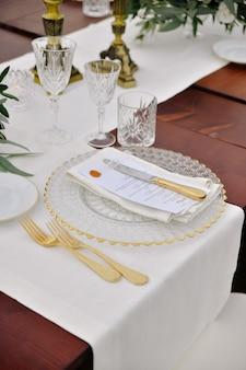 Вид спереди посуды и столовых приборов подается на деревянный стол