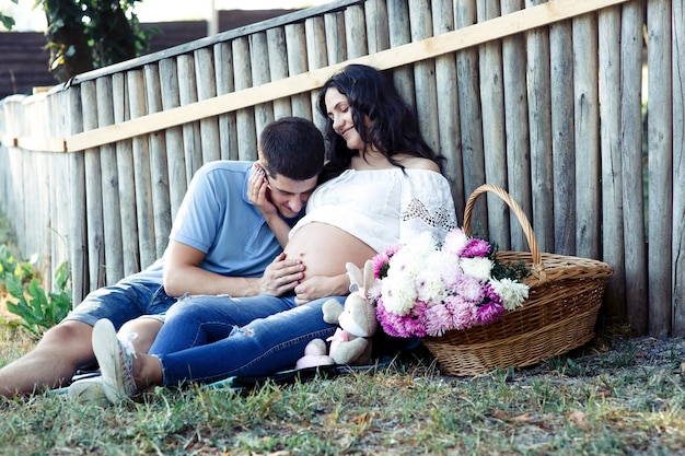 Человек опирается на беременный живот женщины, когда она сидит под деревянным забором