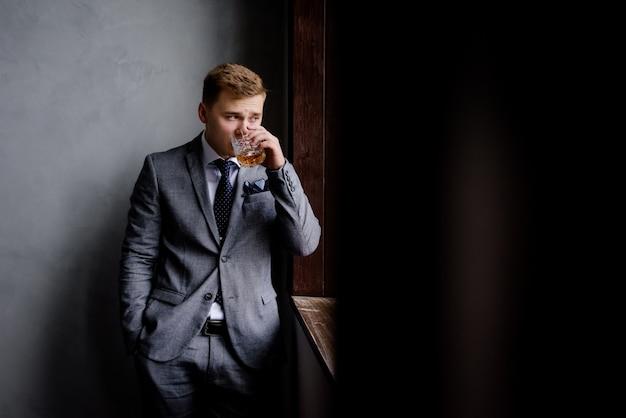 フォーマルな服装でハンサムな男はアルコール飲料を飲んで、窓から見ている