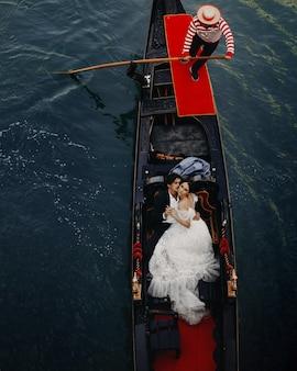 魅力的な新婚夫婦は、ヴェネツィアの豪華なゴンドラに運河に乗っています