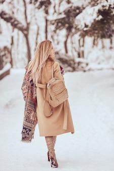 魅力的な女性は冬に通りを歩いています。