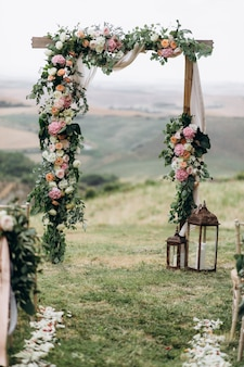 Красивая арка украшена цветочной композицией на открытом воздухе